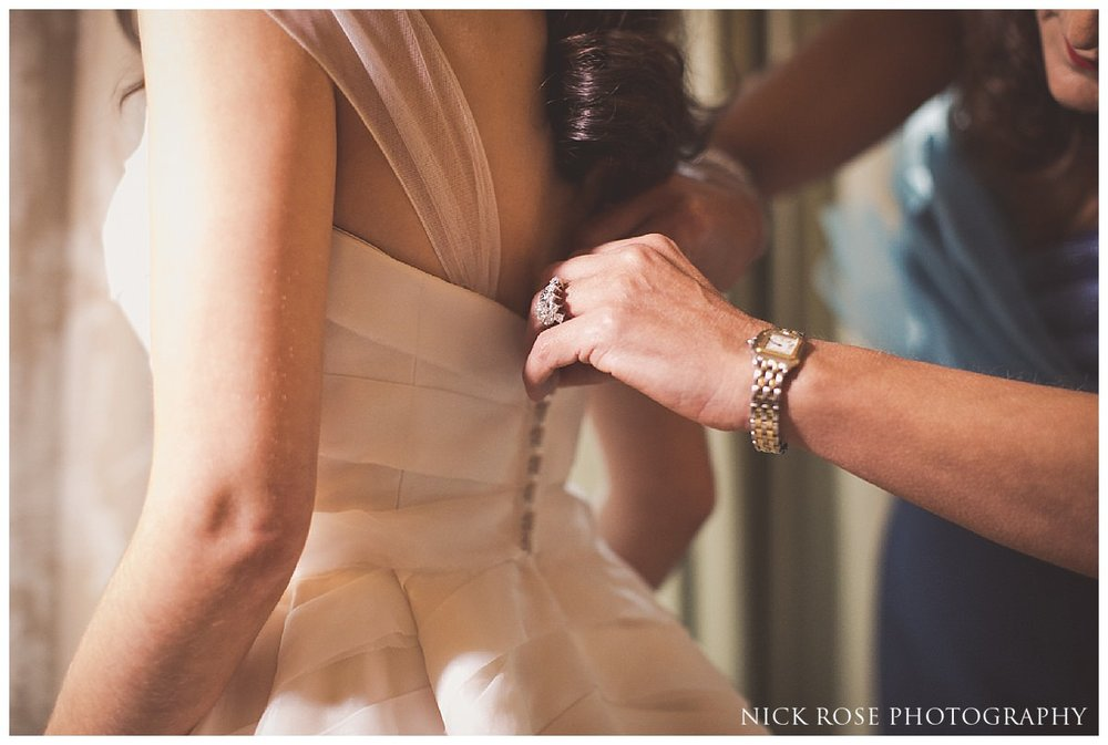 Bride having wedding dress put on before a Savoy London wedding