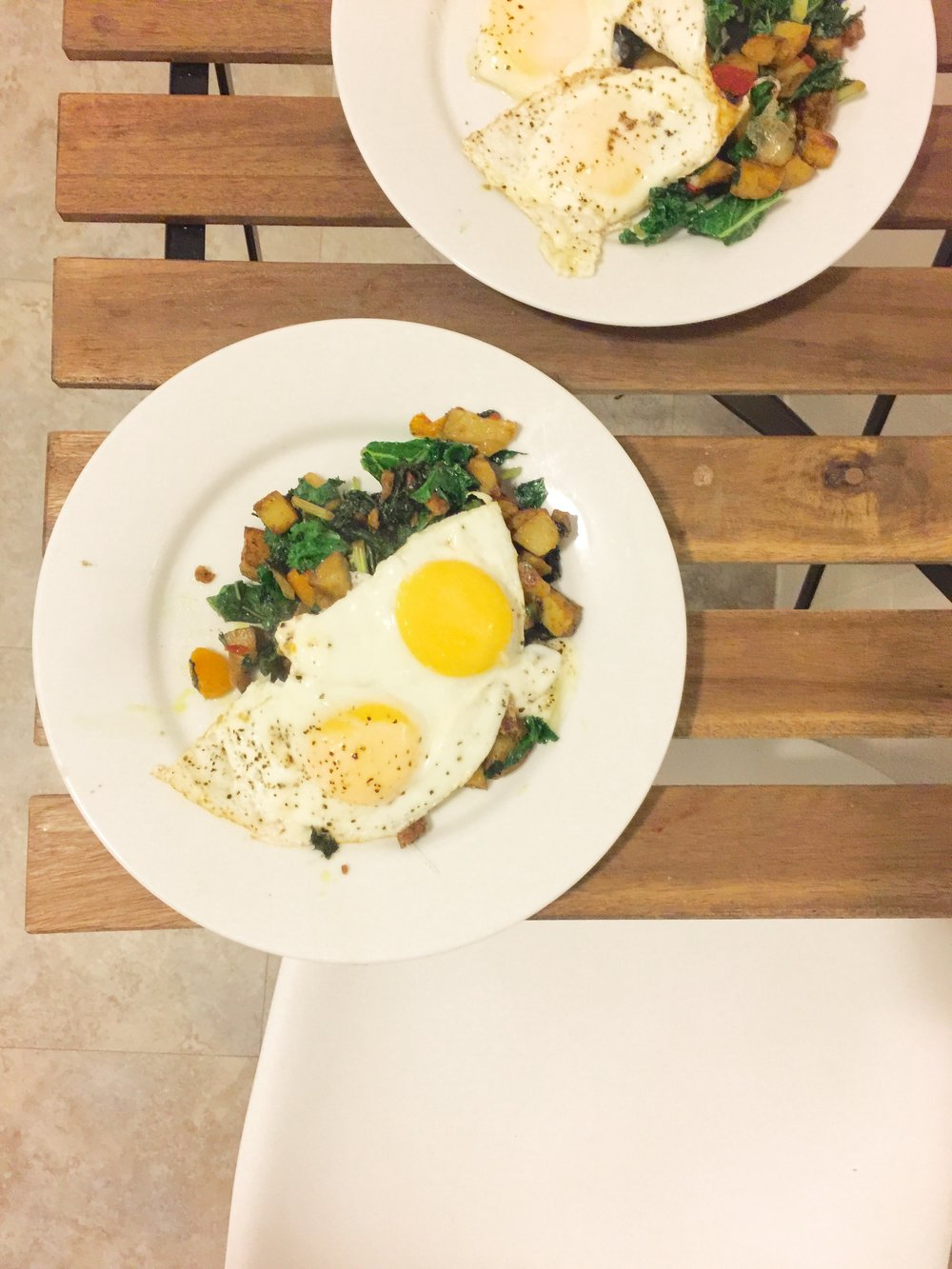 Peppers, curry potatoes, kale and butternut squash hash topped with two eggs