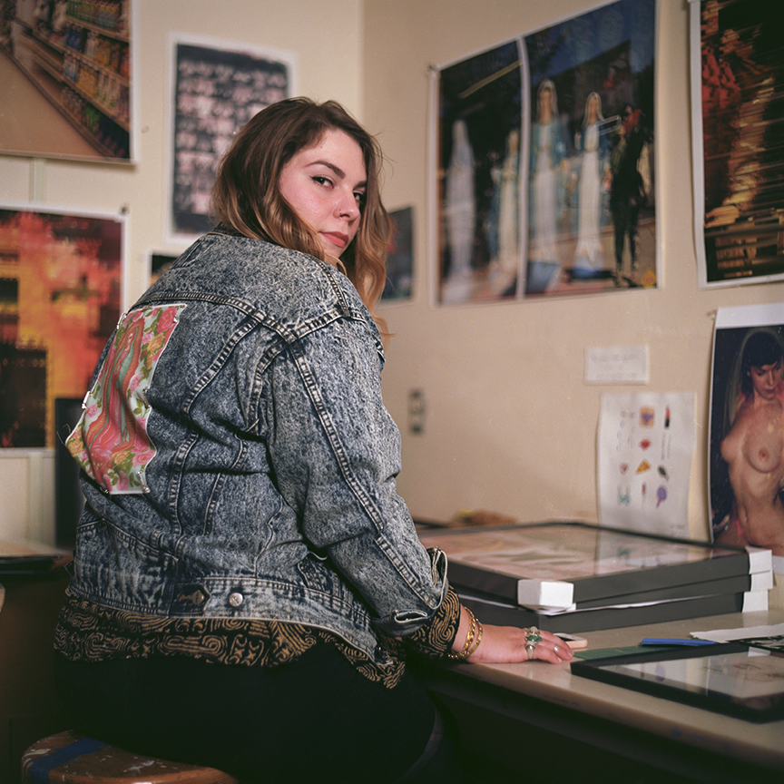 Sitting in her studio Cetto adorns one of her many jean jackets with the Virgin de Guadalupe, a religious theme runs throughout her work.  Photo © Aimee Santos