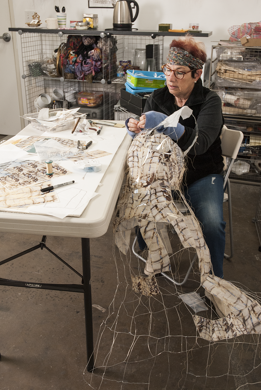 Samuels works on a piece in progress sewing images of architecture onto a dress-like structure in her studio at the Santa Monica Art Studios in Santa Monica, CA.  Photo © Aimee Santos