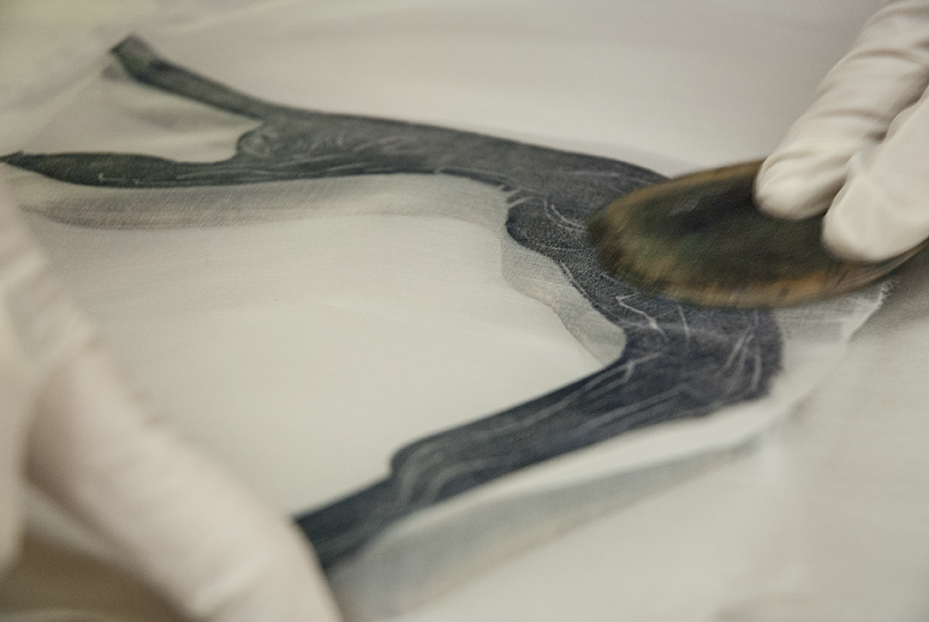Weiss presses a thin sheet of fabric onto a wood cut to transfer the image multiple times.  Photo © Aimee Santos
