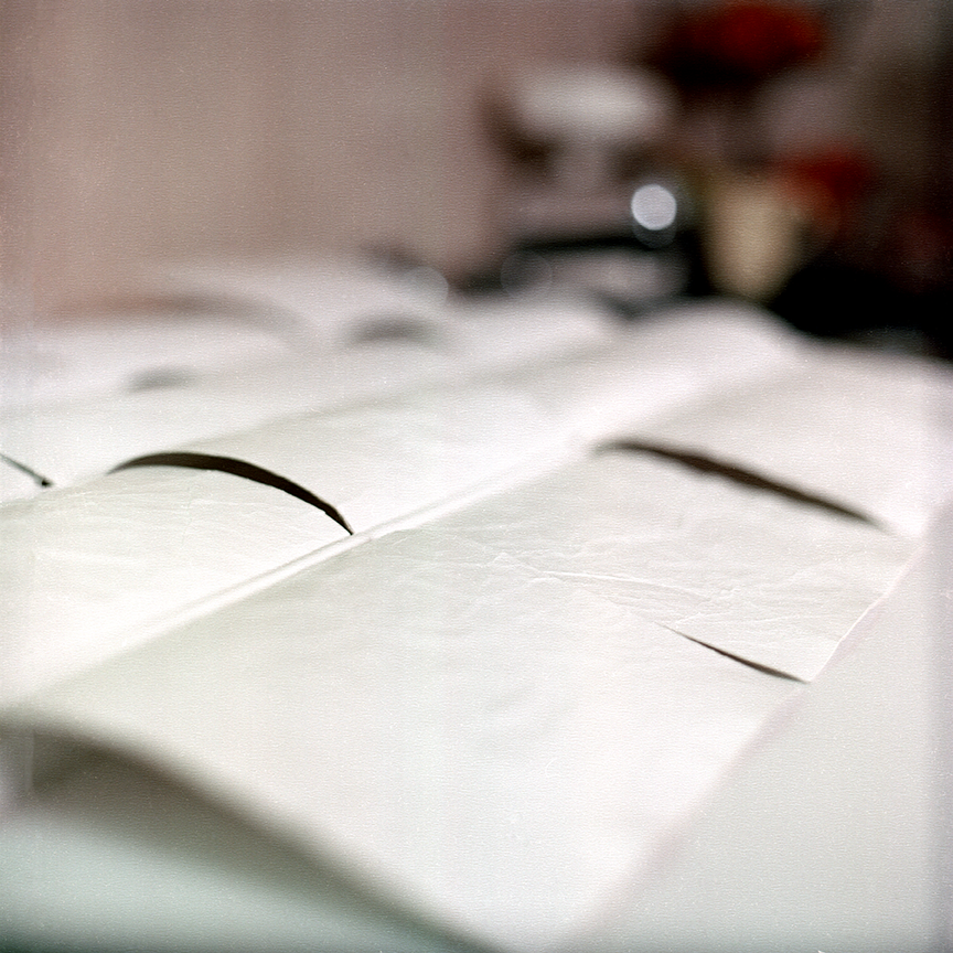 Finished sheets of paper made to look like a white Barcelona Chair line up on the kitchen counter in Tomczyk's home in Pasadena, CA. Photo © Aimee Santos