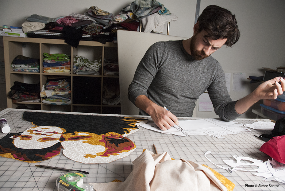 Every step takes time but taking the time makes it right.  Haynes looks over the template of the image he is translating into fabric before proceeding on to the next step.  Photo © Aimee Santos