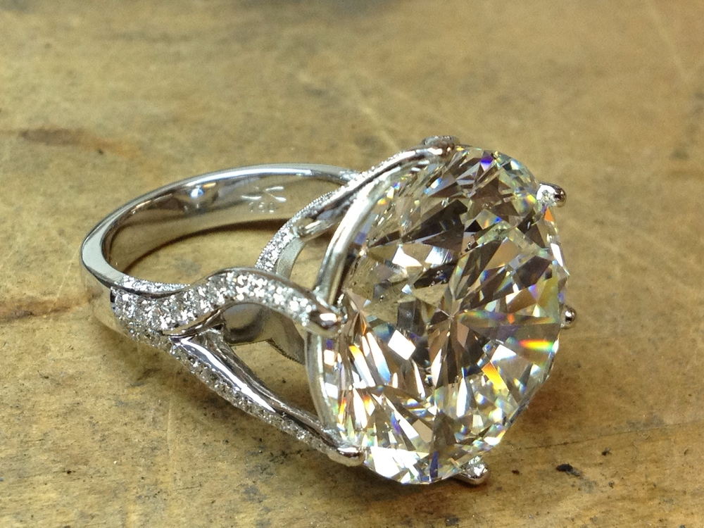 24.12 ct. S.I.2 / H Brilliant Cut Diamond ring in 18k Pd White Gold, adorned by 1.34 ct. T.W. V.S.2 / G Diamond Melee.