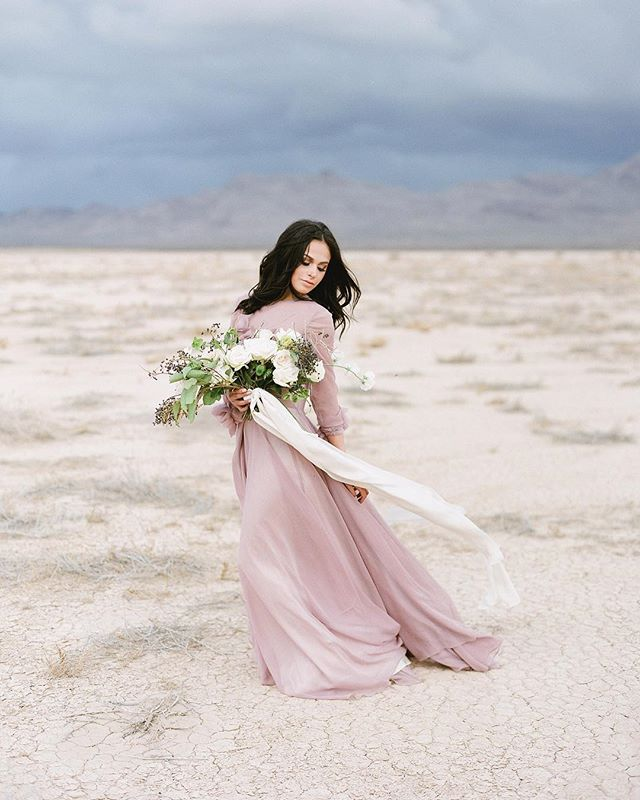 The sun chases her like darkness, hoping to catch up to her light. — j. ironword ⠀⠀⠀⠀⠀⠀⠀⠀⠀ Romance in the desert. This blush @carolhannahbridal gown was such a gorgeous compliment to the muted tones of the desolate landscape. Flawless makeup by @nataliaissa, holding a gorgeous bouquet by @jannabrowndesign. 💕 ⠀⠀⠀⠀⠀⠀⠀⠀⠀ Photographer @jessiebarksdalephotography / Creative direction, styling + florals @jannabrowndesign / Hair and makeup @nataliaissa / Video @annalord / Dresses @carolhannahbridal / Rings @susiesaltzman / Ribbon @silkandwillow / Paper @linenandleaf / Shoes @bellabelleshoes / Ringbox @the_mrs_box / Linen @latavolalinen / Rentals @rsvppartyrentals / Host @charlastorey / Assistants @krystleakin & @katepeasephotography / Sponsors @goodmanfilmlab & @kindredpresets