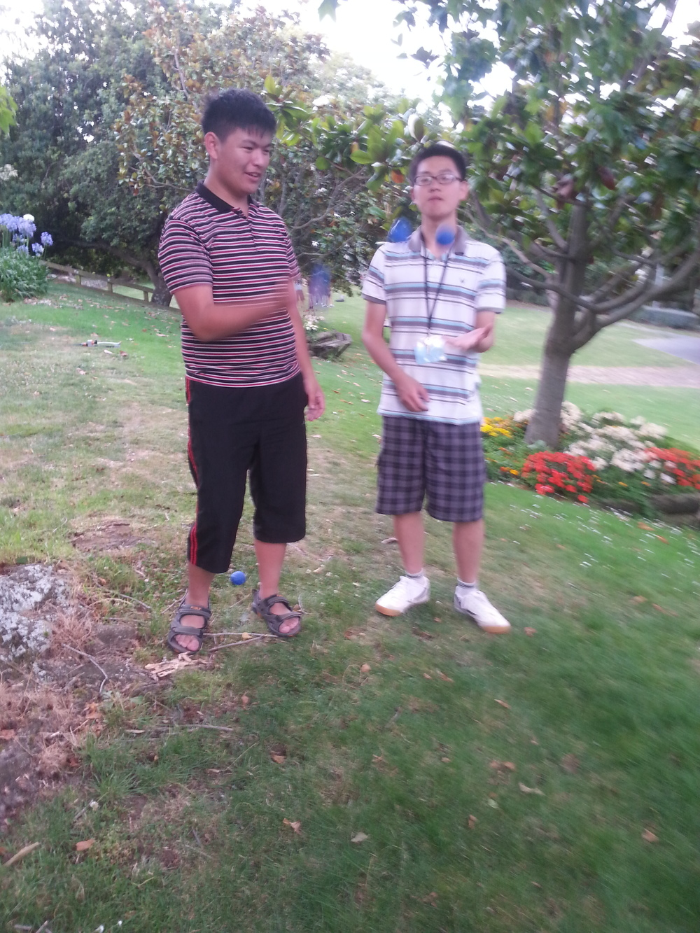Weber Wang (left) and George Han (right) attempting to juggle with half the amount of effort needed for one man to juggle