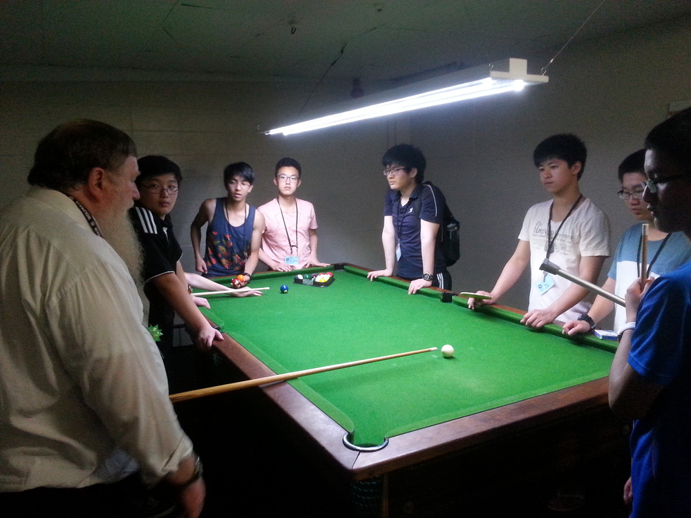 Alan Parris (Chairman of New Zealand Billiards & Snooker Association) teaching the students the correct stance in hitting the cue ball)