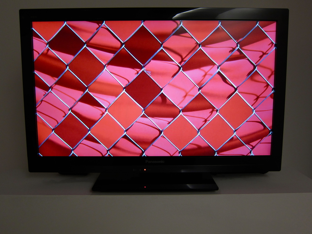 "Noah Klersfeld OCCLF (chain-link fence, orange fabric) Edition of 5 HD Video (5 minutes) 27"" x 16"" (monitor size) 2012"