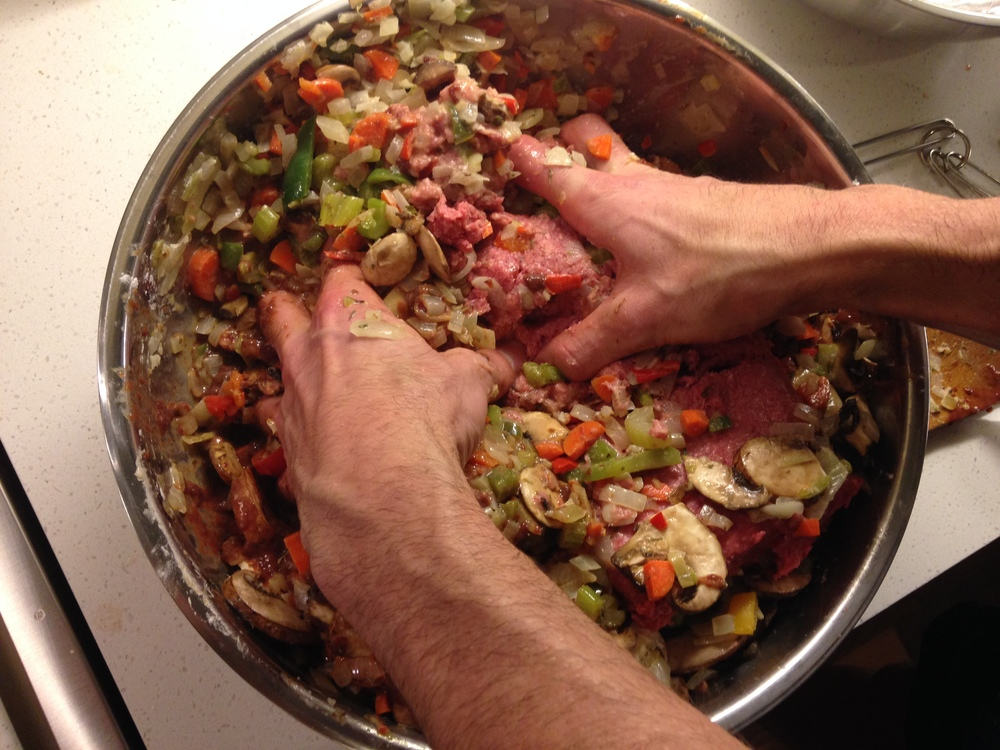 Mixing ground beef with the cooked vegetables
