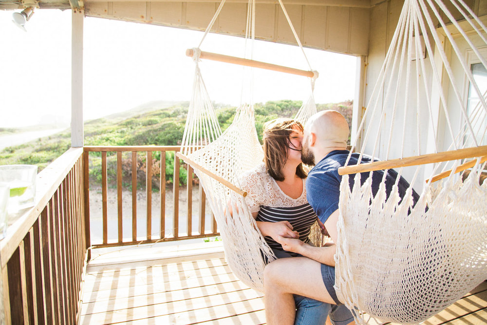Couple kisses while swinging in hammocks on their Oak Island beach house porch