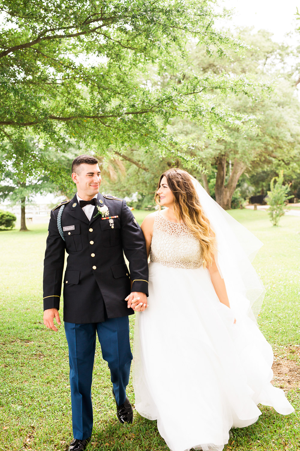 bride and groom stroll under oaks trees in the sunlight