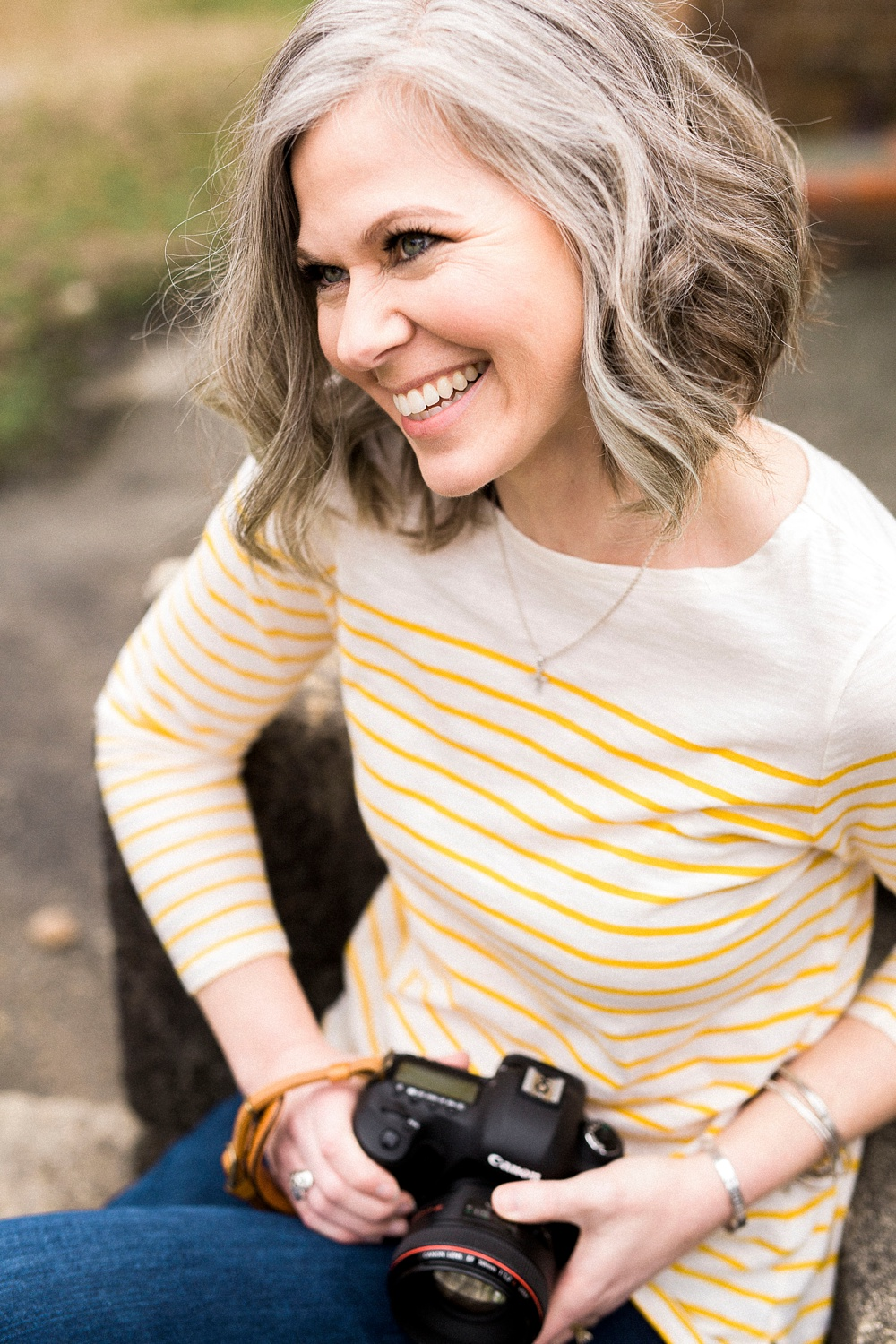 headshot of a female photographer holding her camera and smiling