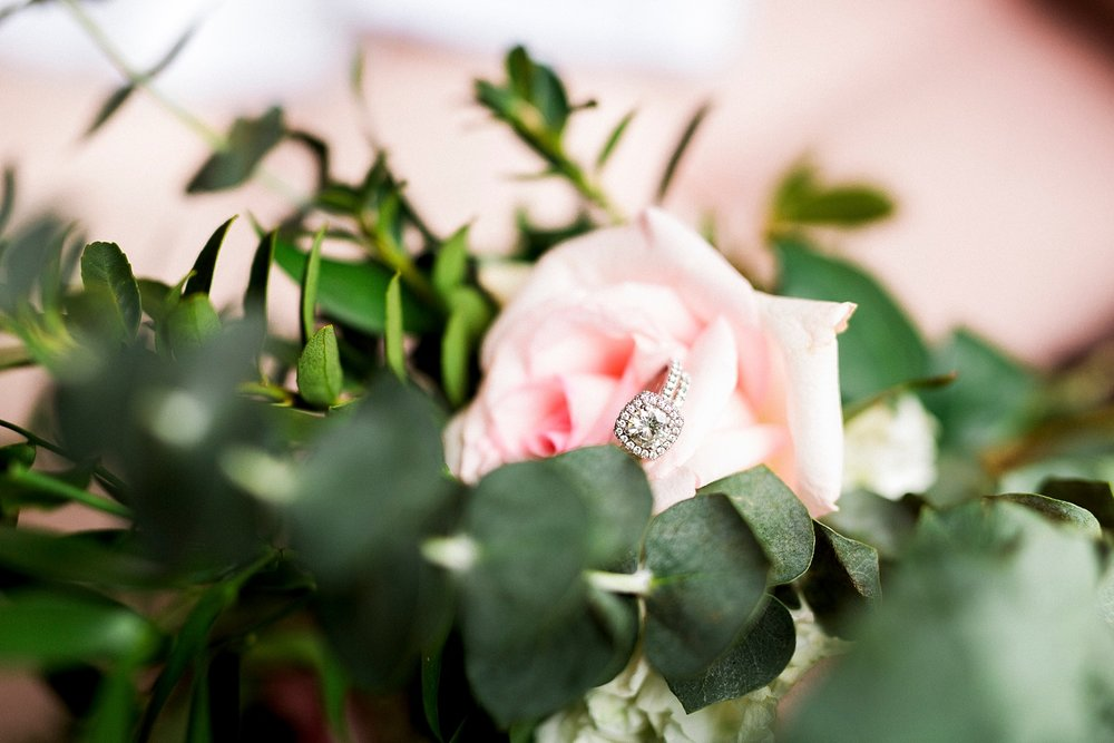 engagement ring rests in a pink rose bloom