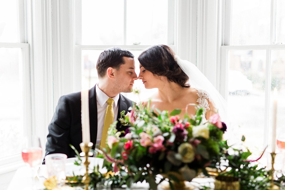 bride and groom touch noses while seated at their sweetheart table