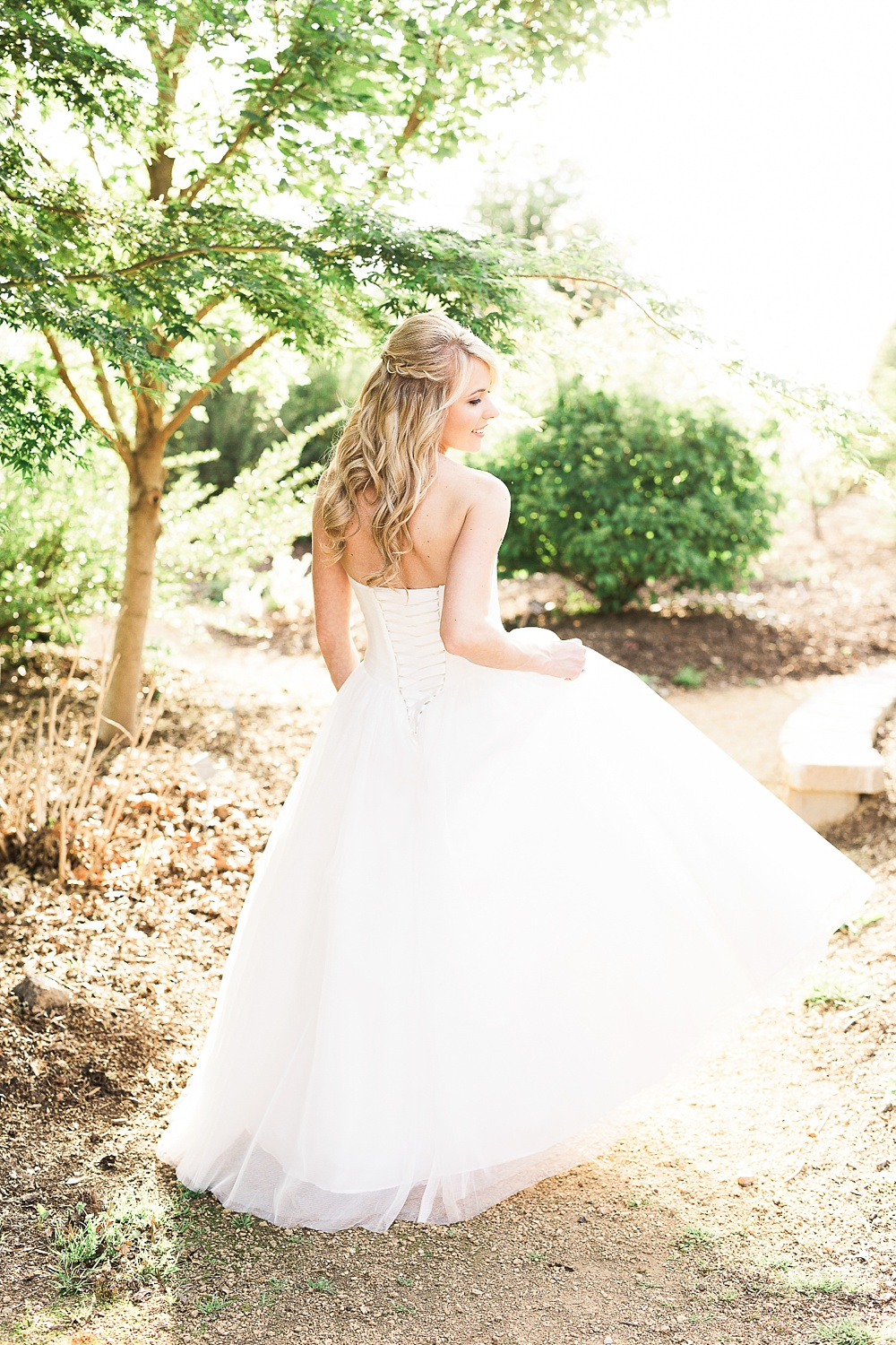 bride smiles and looks over her shoulder in a garden