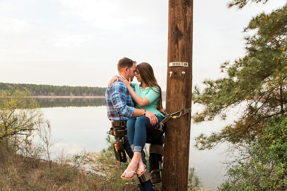 lineman holds his fiance in his harness