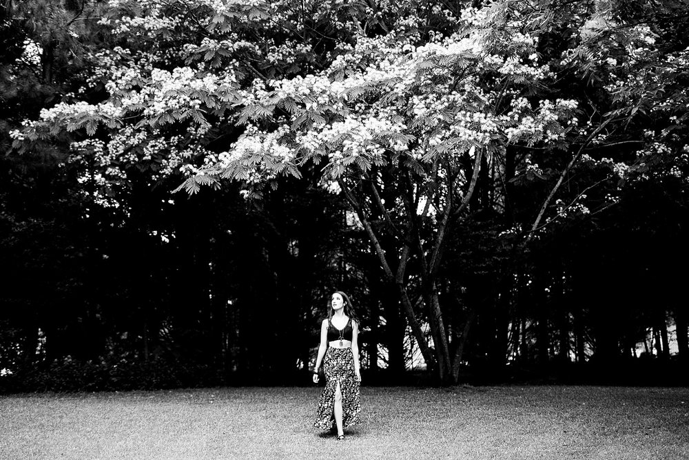 woman poses under a mimosa tree