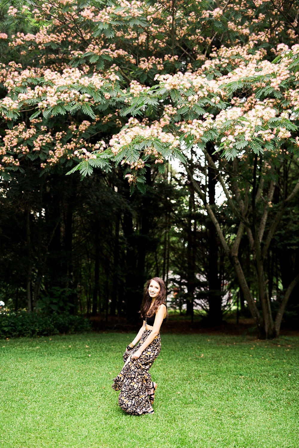 woman twirls her dress under a mimosa tree