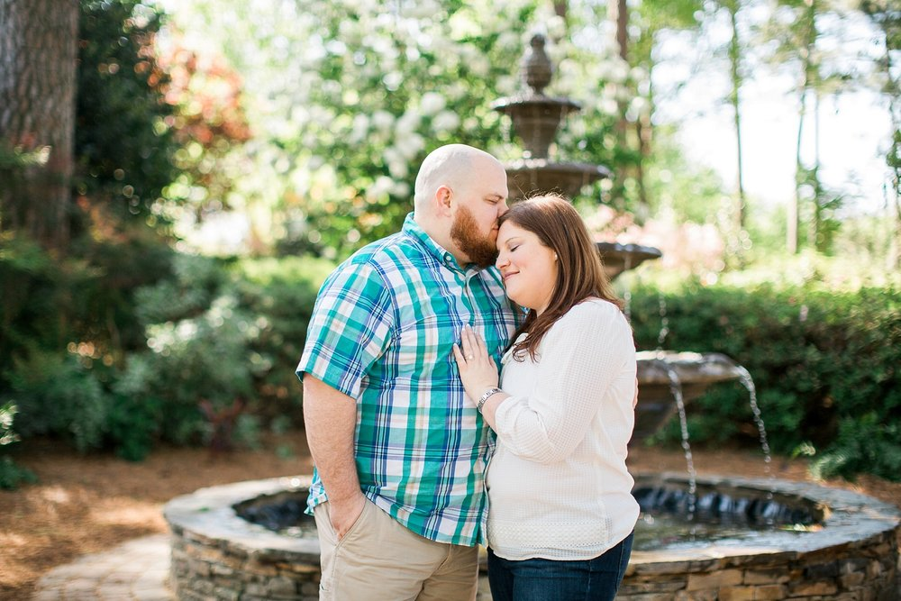 couple poses in front of a fountain in a garden