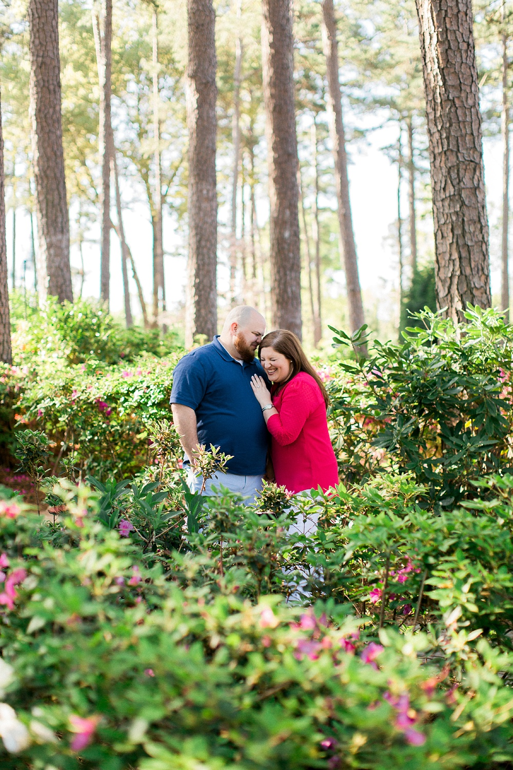 couple laughs in the azalea gardens at their engagement session