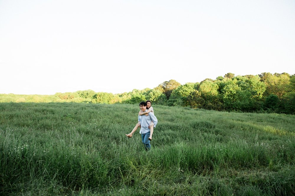couple piggyback rides in a grassy meadow