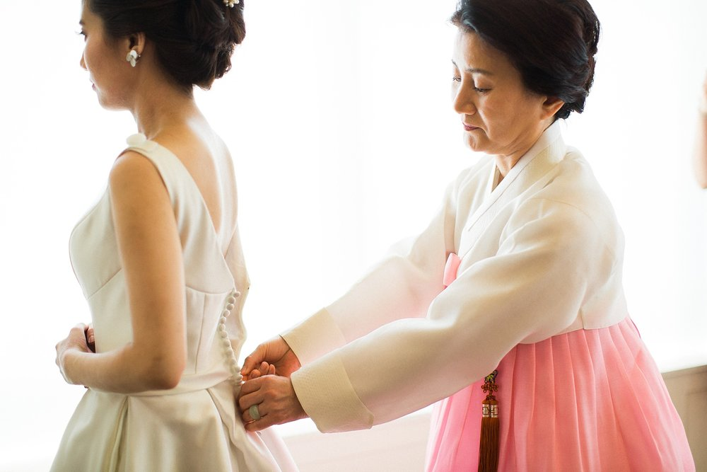 mother dressed in traditional korean garb zips daughter's wedding dress