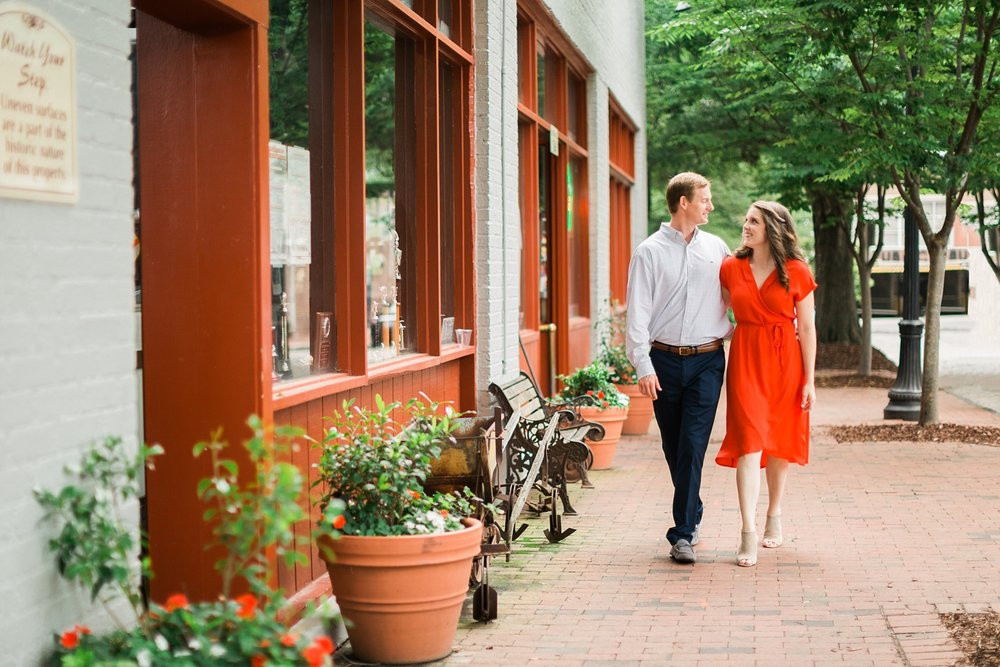 Engaged couple strolls down the sidewalk at Big Ed's in Raleigh's City Market
