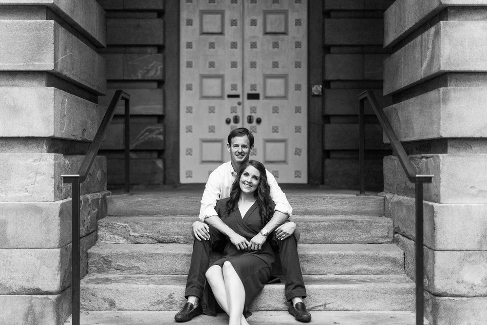 couple sits on the steps of the raleigh capitol building