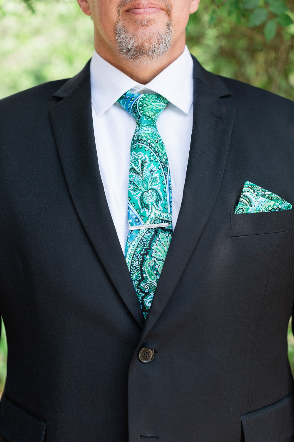detail shot of a groom's blue paisley tie and suit
