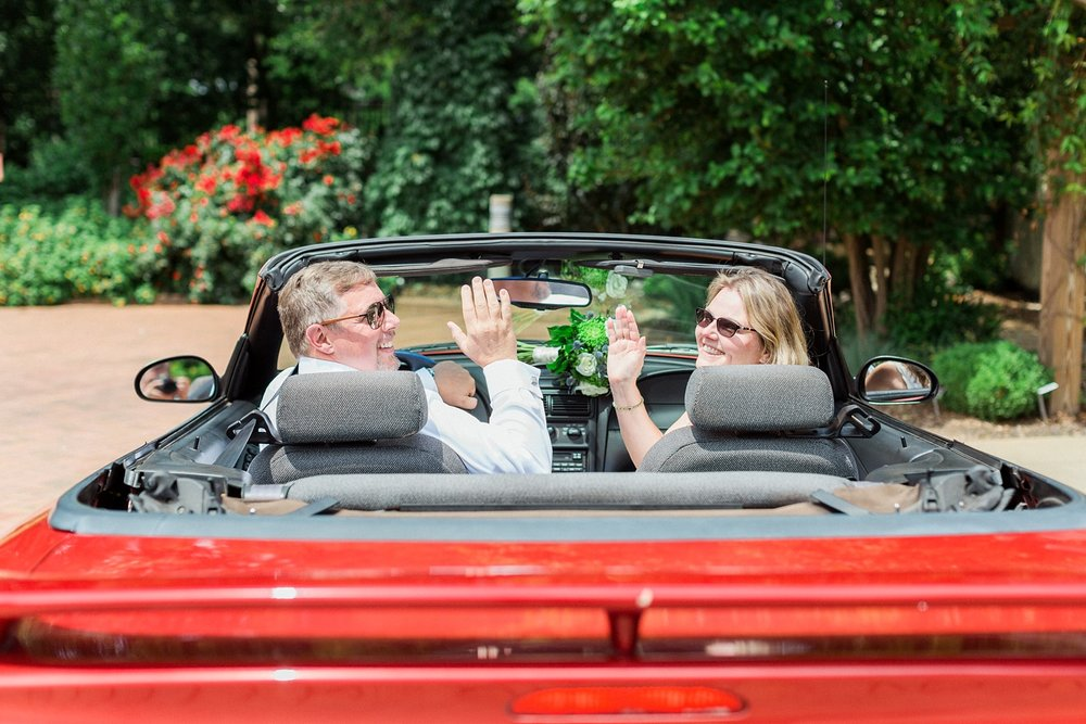 bride and groom wave goodbye as they drive off in a red mustang