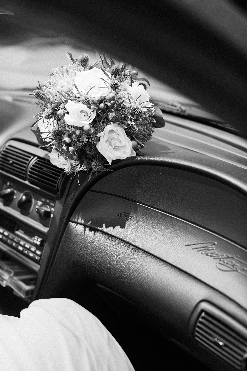 bride's bouquet rests on the dash of her mustang