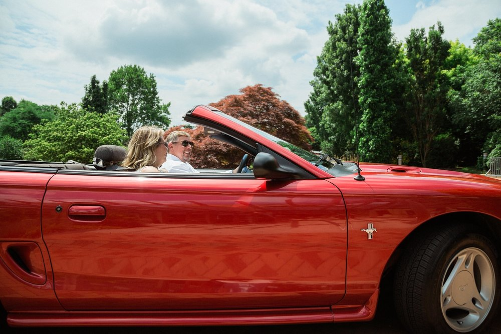 bride and groom drive off in a red mustang