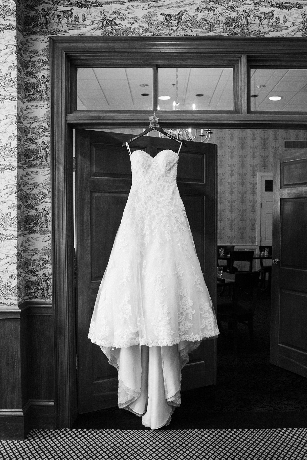 wedding dress hangs in a wooden doorway