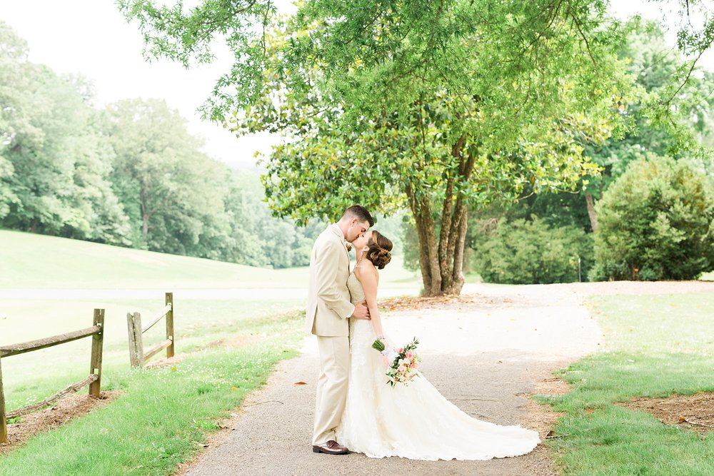 bride and groom kiss under the oaks in front of the first hole greenway
