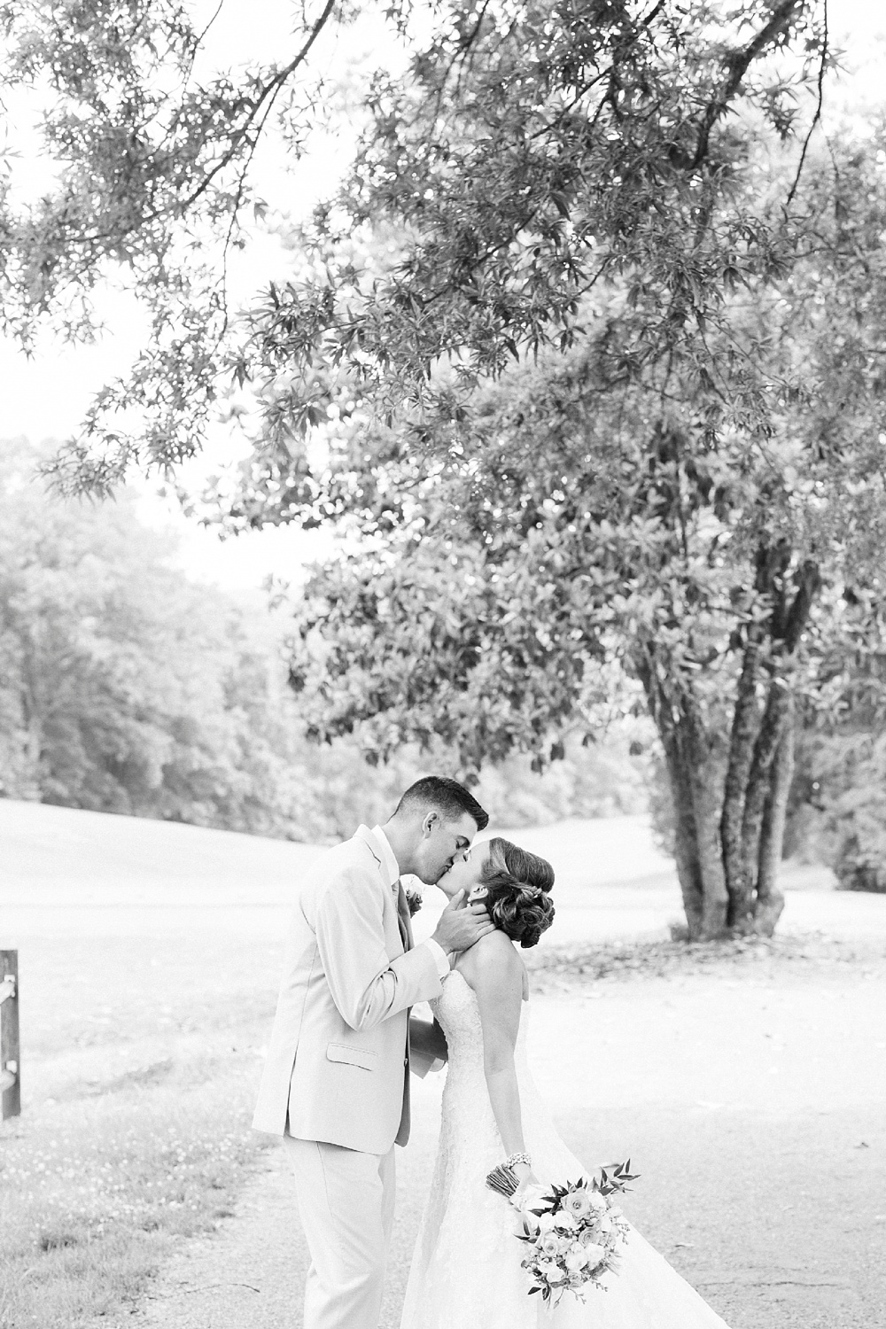 bride and groom kiss under a large oak tree