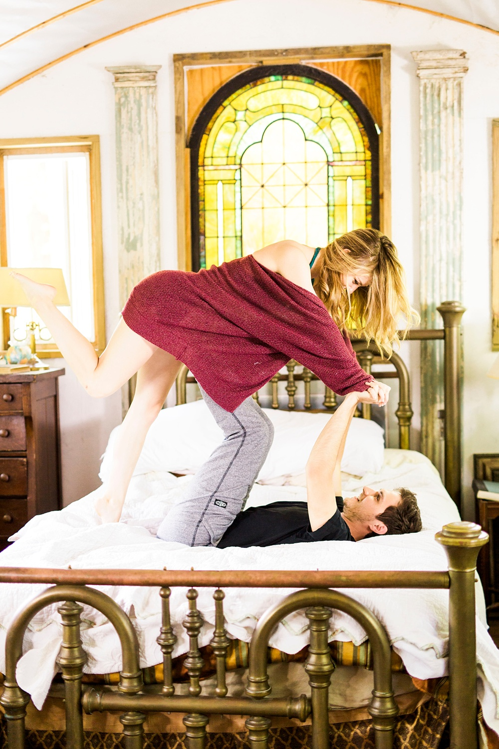 couple plays airplane in their master bedroom