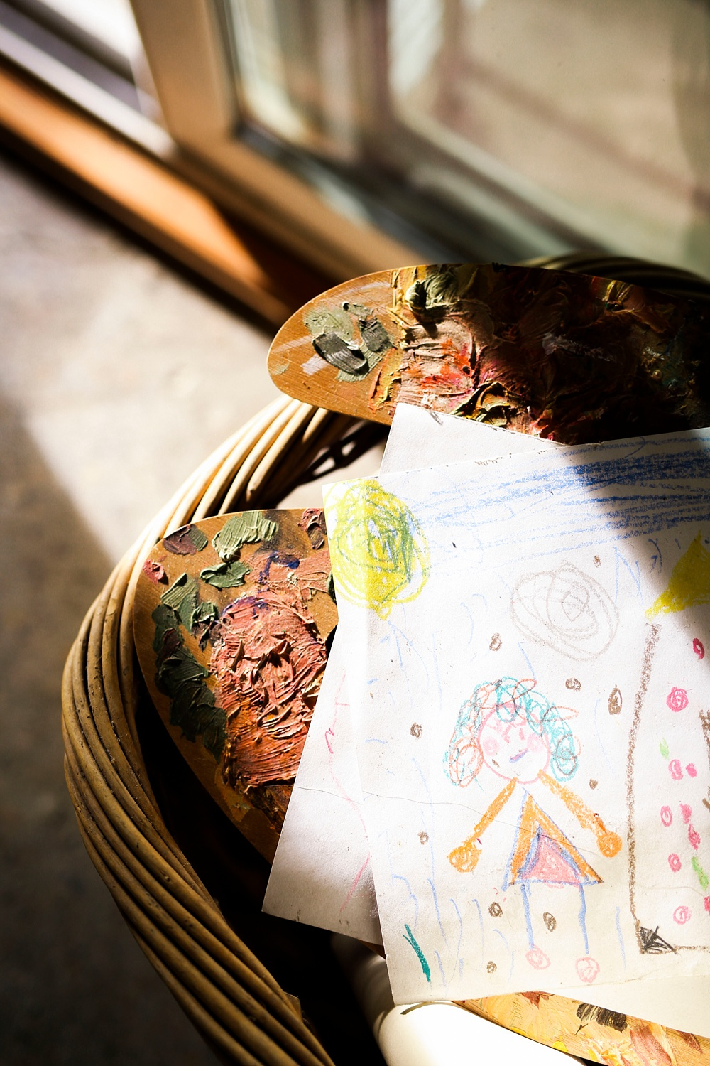 paint palette rests in a wicker basket with a child's drawings