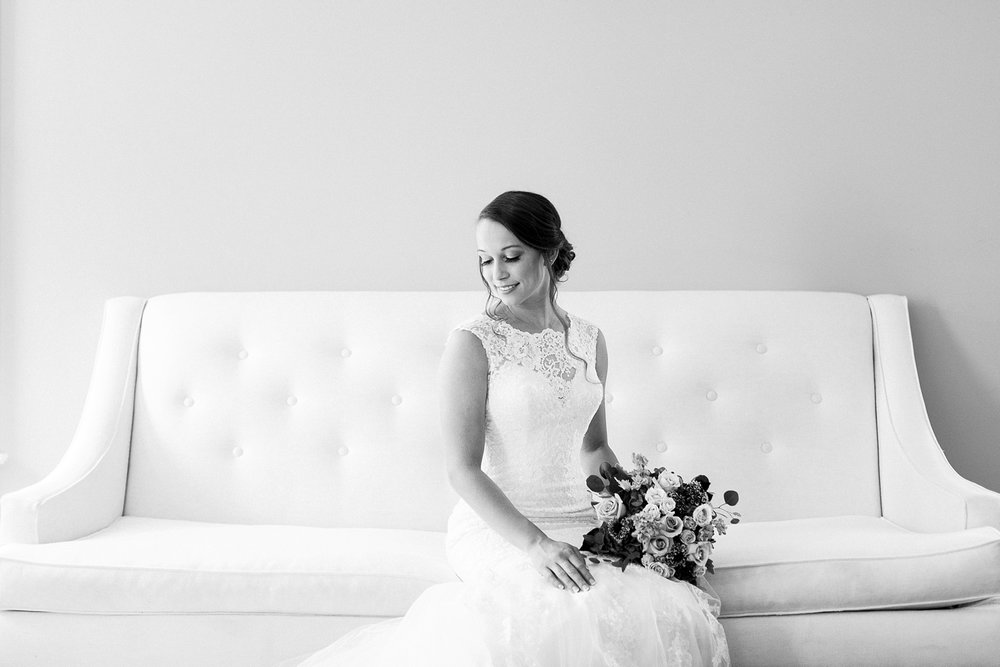 bride sits on white couch for her bridal portrait