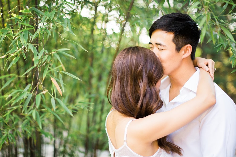 guy kisses fiance on her forehead in a bamboo garden