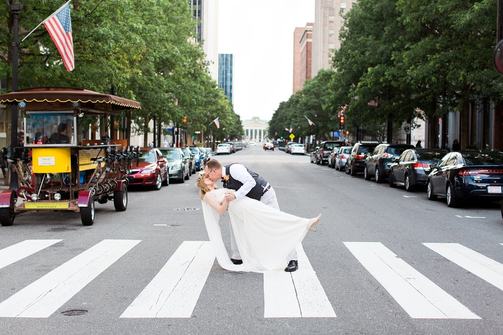 bride and groom dip kiss in downtown raleigh, nc in front of the capital buildling
