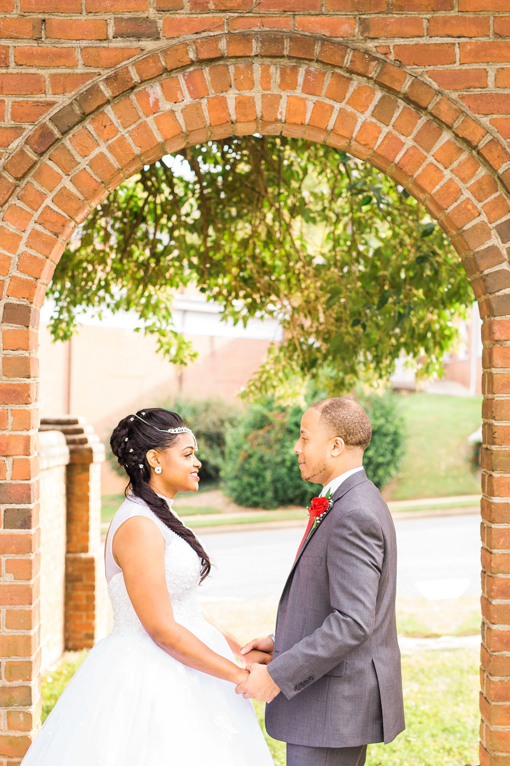 bride and groom hold hands under a brick arch