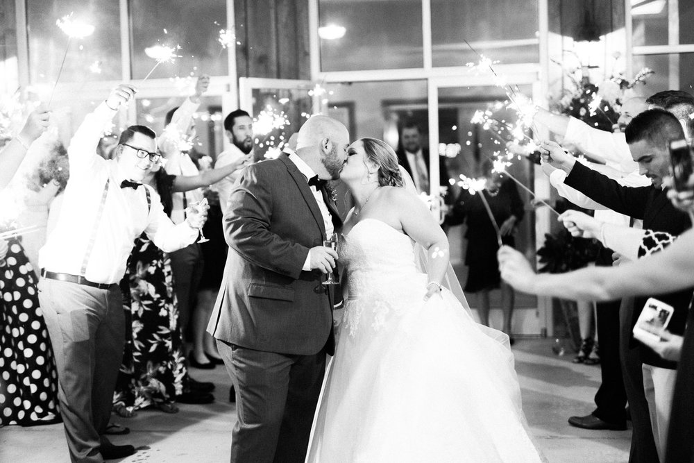 bride and groom kiss while walking through a sparkler exit
