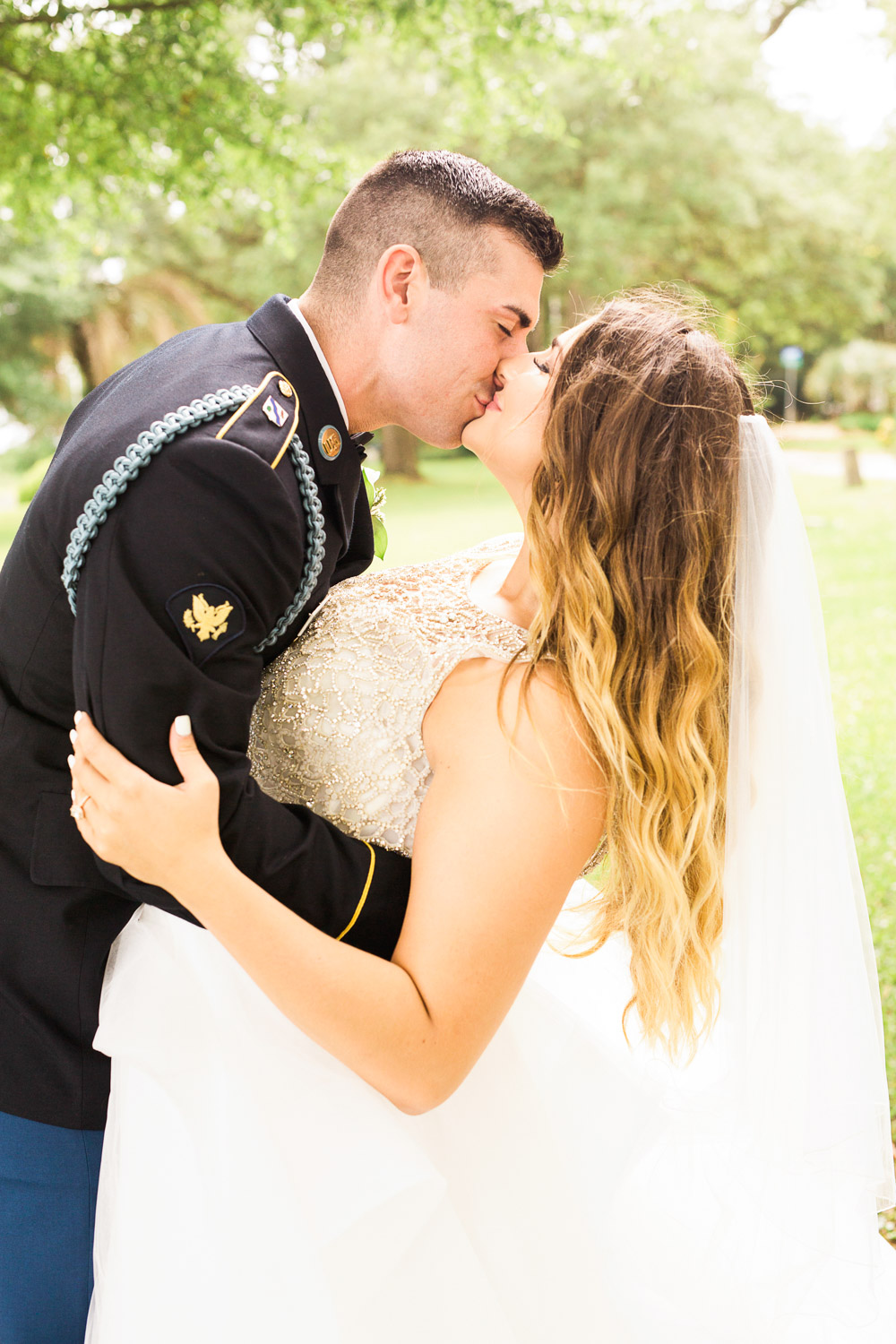 military groom dip kisses his new wife