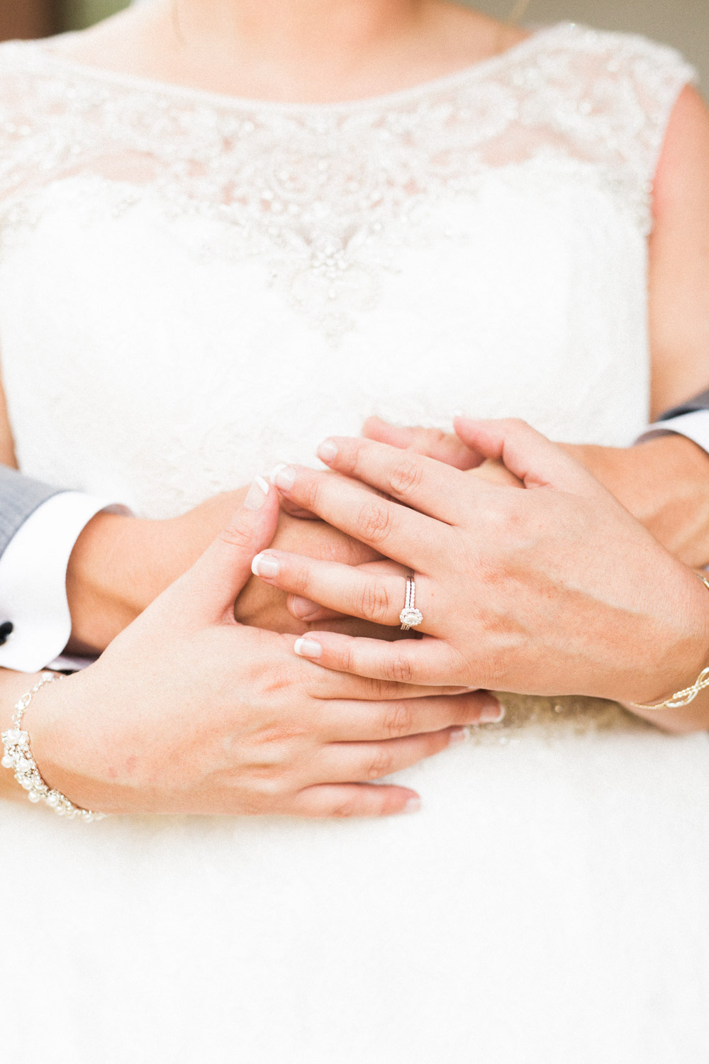bride holds grooms hands that are wrapped around her waist
