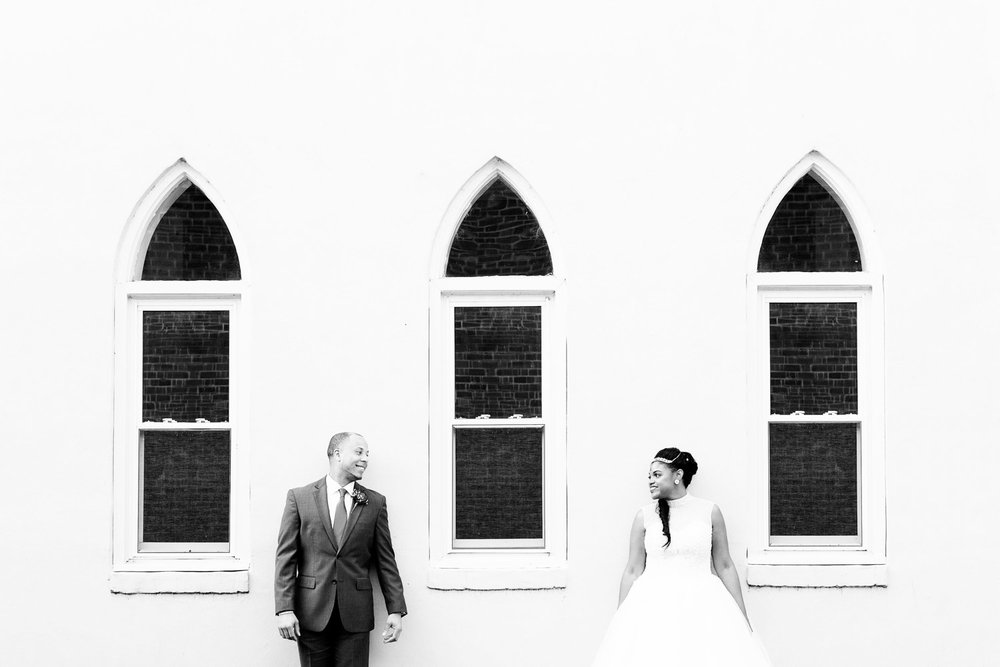 newlyweds stand against a building with 3 arched windows