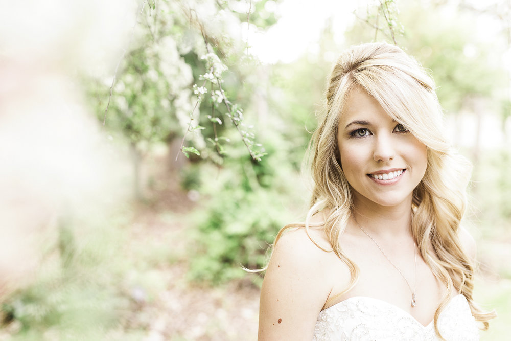bride smiles surrounded by a white flowering tree