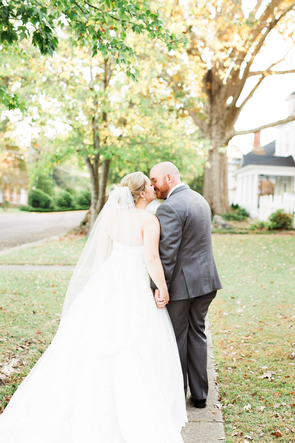 bride and groom kiss while walking down a sidewalk in the fall