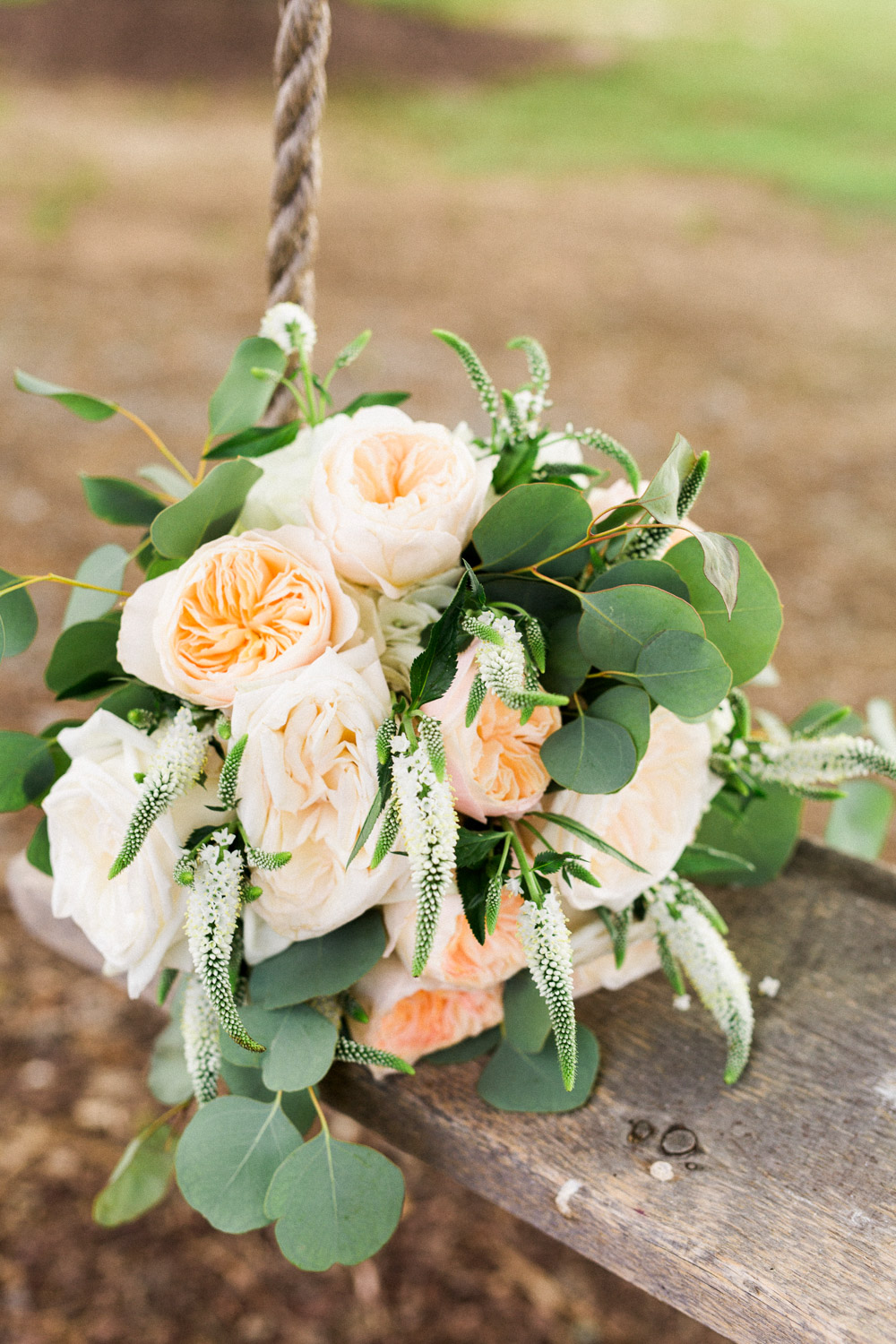 peach peony and eucalyptus bouquet sits on an old rope swing