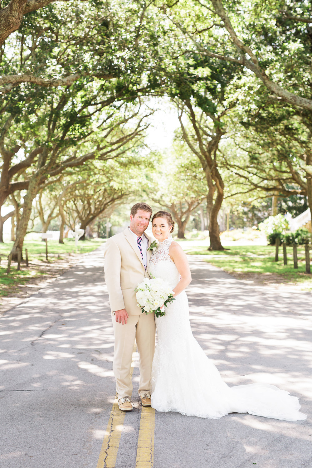 bride and groom on an oak lined road at the beaufort boathouse