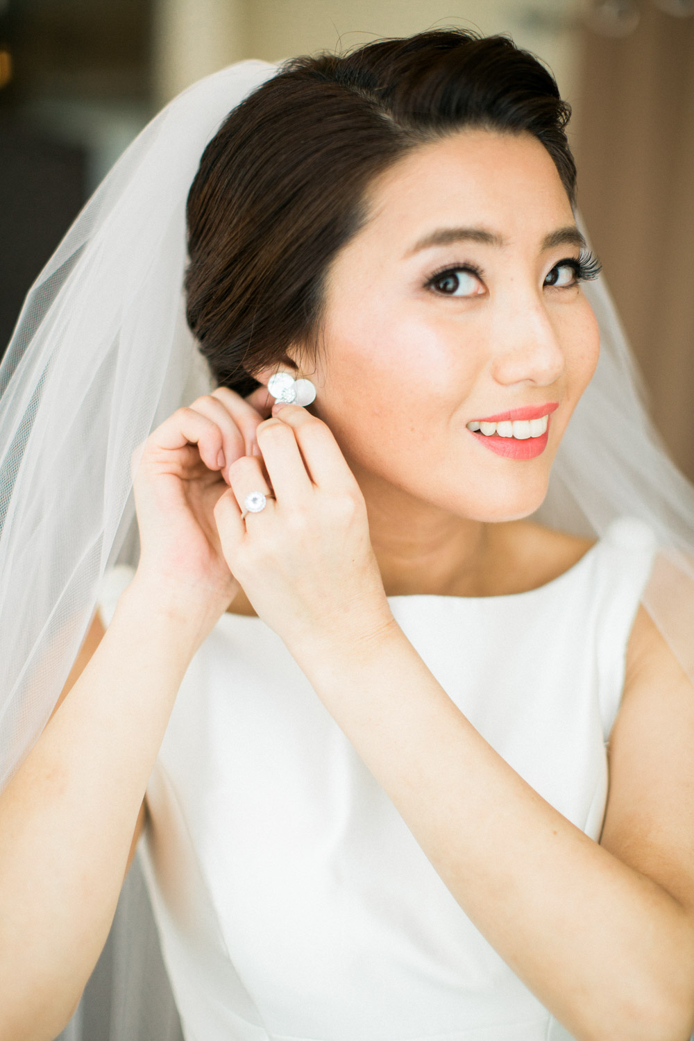 bride puts her earrings in on her wedding day